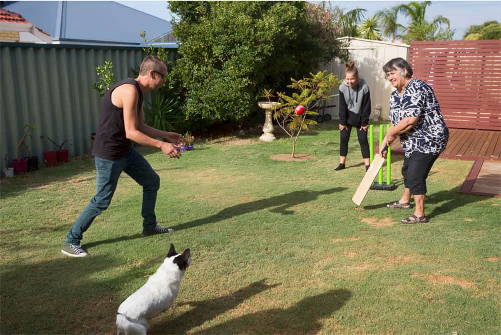 The family dog joins in for a game of backyard cricket
